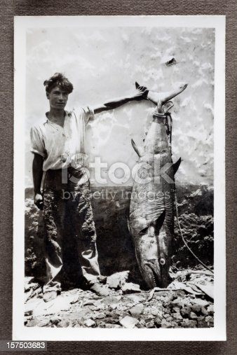 Vintage black and white photograph of a peasant fisherman proudly showing off a large Bluefin Tuna leaning against a wall. Some dust and scratches which convey age of original image, taken in Mauritius, 1942.