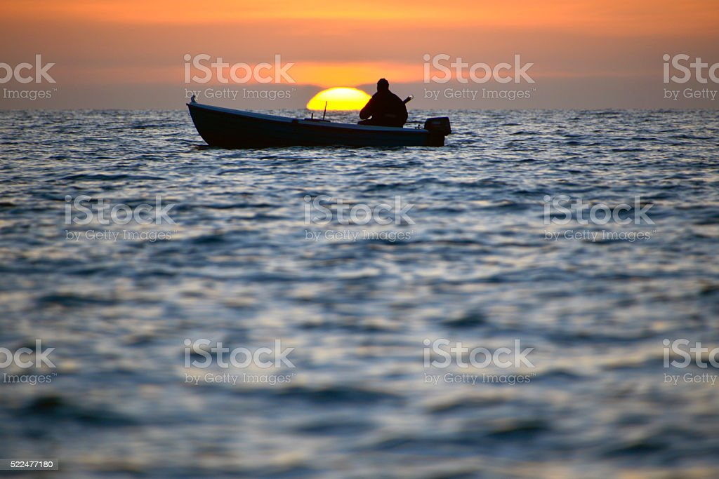 fisherman with boat at sea at beautiful sunset - Royalty-free Adult Stock Photo