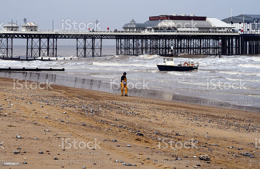 Fisherman with boat on Cromer beach, Norfolk stock photo