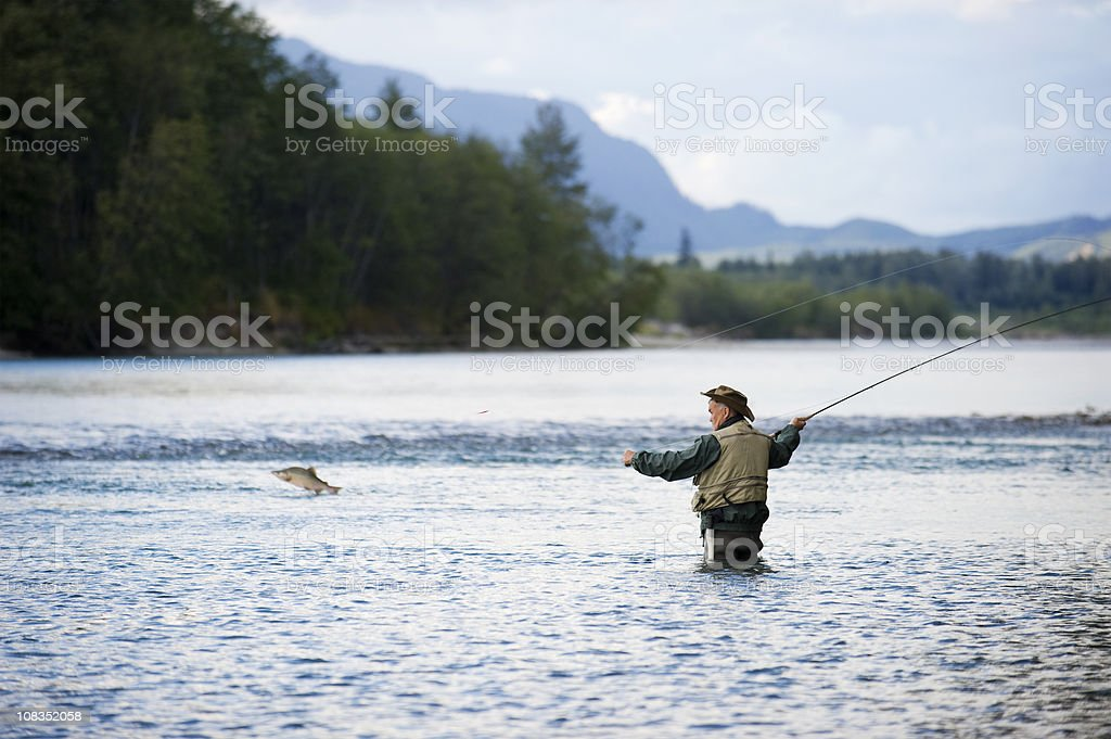 Fisherman with fish jumping stock photo
