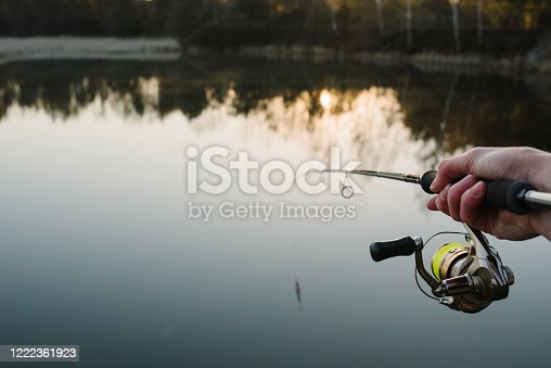 951984746 istock photo Fisherman with fishing rod in his hand catches fish on a boat. Fishing Day. Spinning in hand on pond background. 1222361923