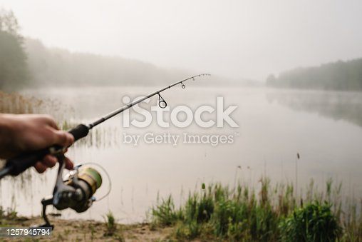 istock Fisherman with rod, spinning reel on river bank. Fishing for pike, perch, carp. Fog against the backdrop of lake. Background misty morning. wild nature. The concept of a rural getaway. Fishing day. 1257945794