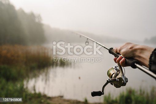 istock Fisherman with rod, spinning reel on river bank. Fishing for pike, perch, carp. Fog against the backdrop of lake. Background misty morning. wild nature. The concept of a rural getaway. Fishing day. 1257945806
