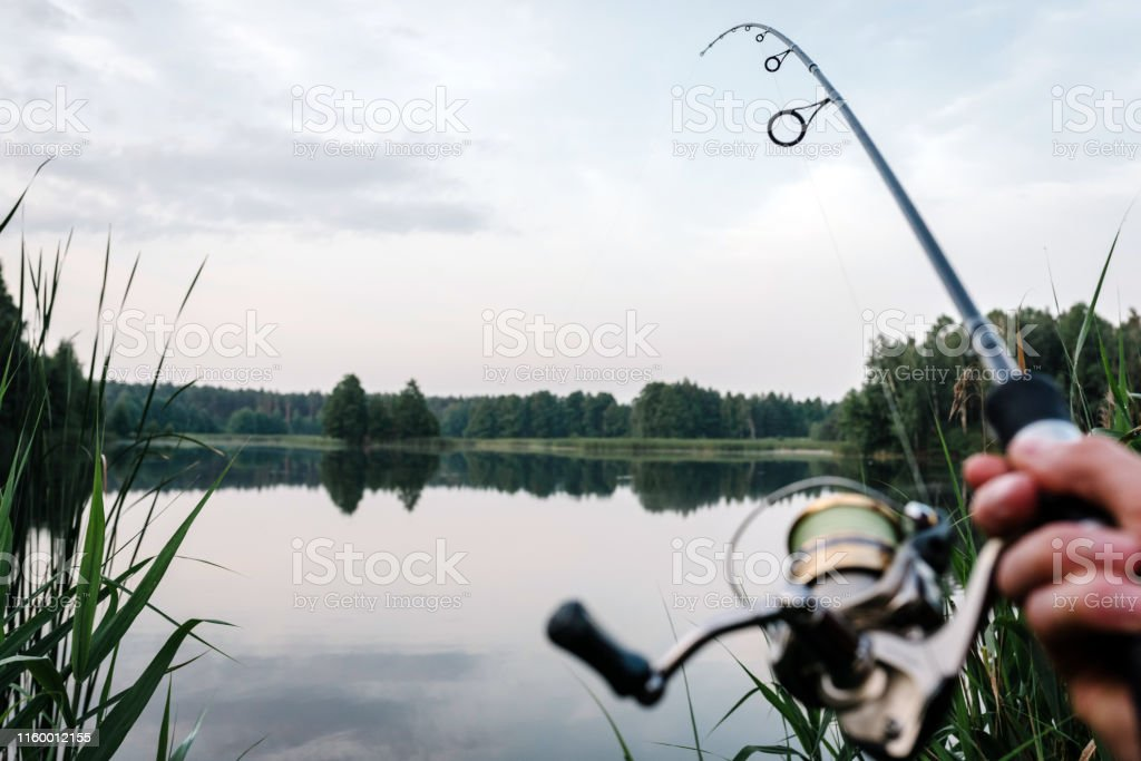 Fisherman With Rod Spinning Reel On The River Bank Fishing