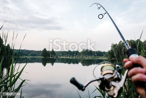 951984746 istock photo Fisherman with rod, spinning reel on the river bank. Fishing for pike, perch, carp. Fog against the backdrop of lake. background Misty morning. wild nature. Article about fishing day. 1160012155