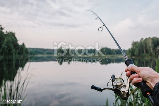 951984746 istock photo Fisherman with rod, spinning reel on the river bank. Fishing for pike, perch, carp. Fog against the backdrop of lake. background Misty morning. wild nature. The concept of a rural getaway. 1160012157