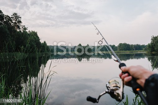 951984746 istock photo Fisherman with rod, spinning reel on the river bank. Fishing for pike, perch, carp. Fog against the backdrop of lake. background Misty morning. wild nature. The concept of a rural getaway. 1160012167
