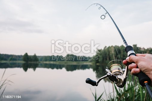 951984746 istock photo Fisherman with rod, spinning reel on the river bank. Fishing for pike, perch, carp. Fog against the backdrop of lake. background Misty morning. wild nature. Article about fishing day. 1160571194