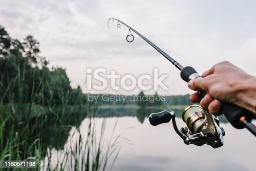 951984746 istock photo Fisherman with rod, spinning reel on the river bank. Fishing for pike, perch, carp. Fog against the backdrop of lake. background Misty morning. wild nature. The concept of a rural getaway. 1160571198
