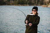 istock Fisherman with rod, spinning reel on the river bank. Fishing for pike, perch, carp. Woman catching a fish, pulling rod while fishing at the weekend. Girl fishing on lake, pond with text space. 1219909992