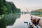 istock Fisherman with rod, spinning reel on the river bank. Sunrise. Fishing for pike, perch, carp. Fog against the backdrop of lake. background Misty morning. wild nature. The concept of a rural getaway. 1092160614