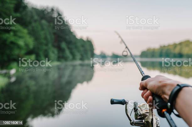 Photo of Fisherman with rod, spinning reel on the river bank. Sunrise. Fishing for pike, perch, carp. Fog against the backdrop of lake. background Misty morning. wild nature. The concept of a rural getaway.
