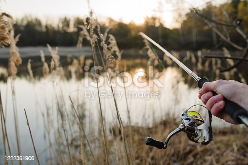951984746 istock photo Fisherman with rod, spinning reel on the river bank. Sunrise. Fishing for pike, perch, carp. Fog against the backdrop of lake. background Misty morning. wild nature. The concept of a rural getaway. 1222361906