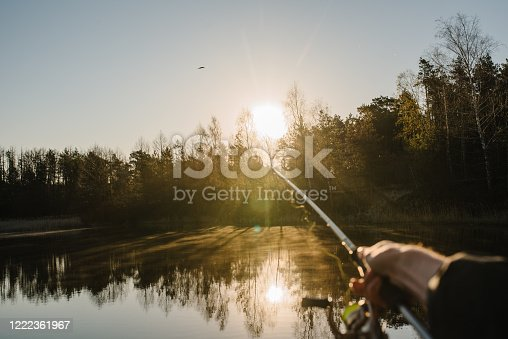 951984746 istock photo Fisherman with rod, spinning reel on the river bank. Sunrise. Fishing for pike, perch, carp. Fog against the backdrop of lake. background Misty morning. wild nature. The concept of a rural getaway. 1222361967