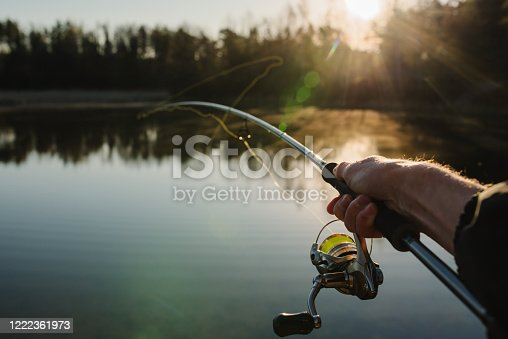 951984746 istock photo Fisherman with rod, spinning reel on the river bank. Sunrise. Fishing for pike, perch, carp. Fog against the backdrop of lake. background Misty morning. wild nature. The concept of a rural getaway. 1222361973
