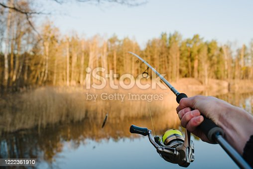 951984746 istock photo Fisherman with rod throws bait into the water on river bank. Fishing for pike, perch. Background wild nature. Concept of rural getaway. Man catching a fish on lake or pond with text space. Fishing day. 1222361910