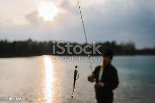 914030378 istock photo Fisherman with rod throws bait into the water on river bank. Fishing for pike, perch, carp. Background wild nature. The concept of rural getaway. Woman catching a fish on lake or pond with text space. 1224641638