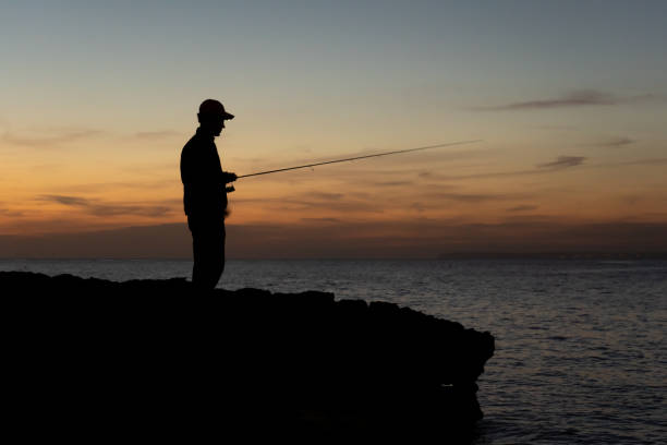A fisherman with the rod at sunset against the light in Majorca, Spain stock photo