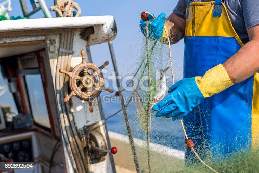 155674939istockphoto Fisherman working on his boat 692892594