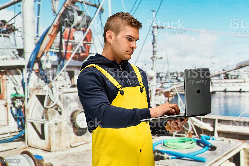 Fisherman working on laptop in fishing boat stock photo