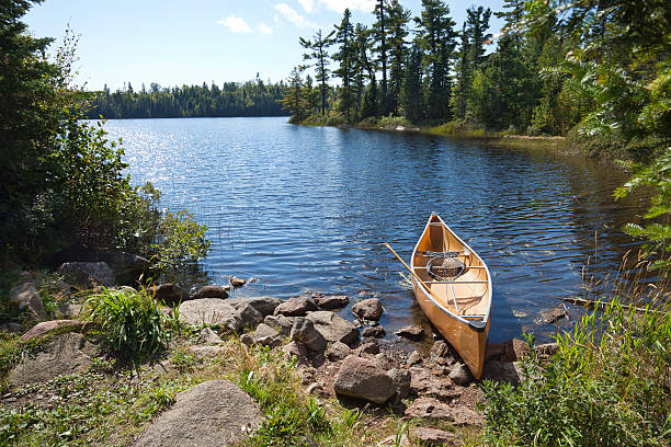 Fisherman's canoe on rocky shore in northern Minnesota lake A yellow fisherman's canoe on a rocky shore of a northern Minnesota lake minnesota stock pictures, royalty-free photos & images