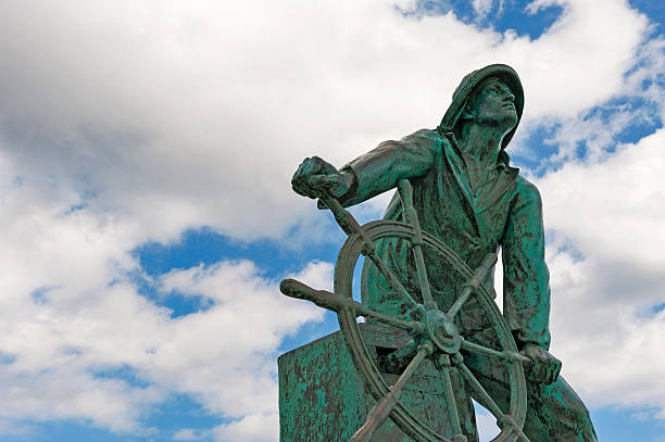 Fishermans Memorial This very moving statue faces the Ocean and Cape Ann in Gloucester, Massachusetts and is a very popular landmark. It shows respect and rememberance to the many Fishermen that have lost their lives over the years from this area. gloucester massachusetts stock pictures, royalty-free photos & images