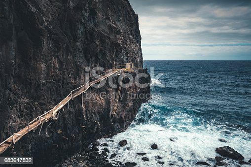 View on a large cliff with spectacular wooden path used by fishermen (Madeira Island).
