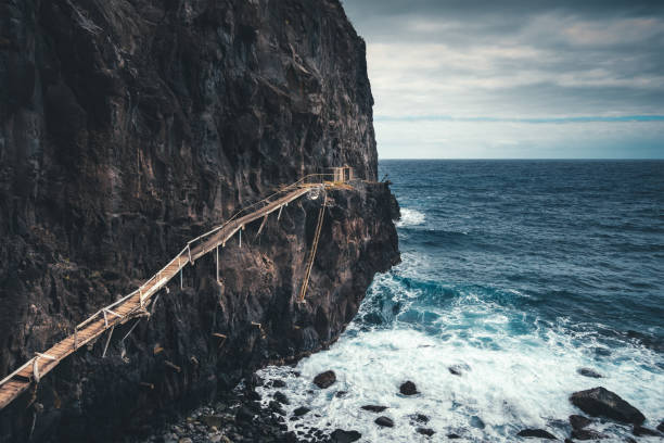 Fisherman's Path On Madeira Island View on a large cliff with spectacular wooden path used by fishermen (Madeira Island). narrow stock pictures, royalty-free photos & images
