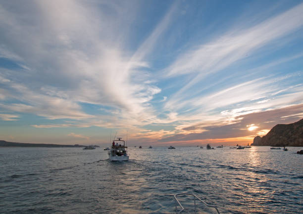 Fishermans sunrise view of fishing boat going out for the day past Lands End in Cabo San Lucas in Baja California Mexico BCS stock photo