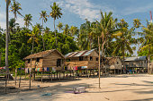 Island of Borneo, Malaysia - November 5, 2019: Fisherman's village, sandy beach and palm trees, island Sipadan close to Semporna city on Borneo.