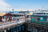 Monterey, California, USA-August 1, 2014: Pier in the Harbour of Monterey, California, with some boats, stores, some people, and an office for whale watching. A USA flag on the left lower corner.