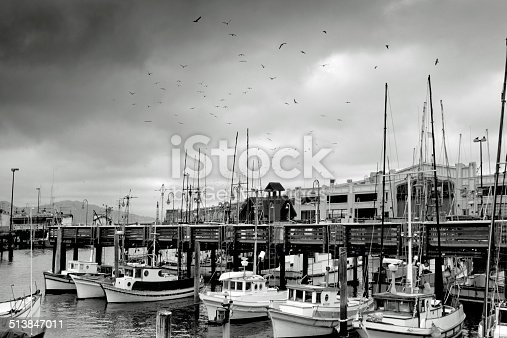 The fishing fleet at Fisherman's Wharf San Francisco with a dark foreboding sky full of seagulls just after dawn.
