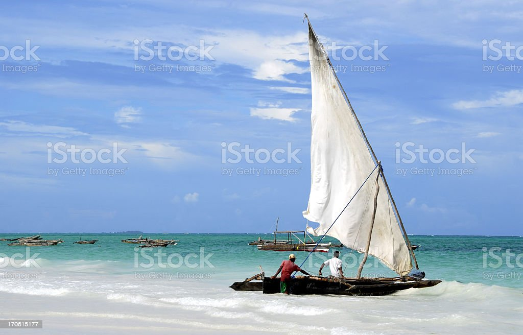 Fishermen and their dhow, Kiwengwa Beach,Zanzibar,Tanzania stock photo