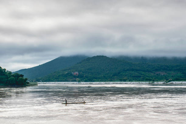 Fishermen are on a boat in the lake and behind are mountains. stock photo