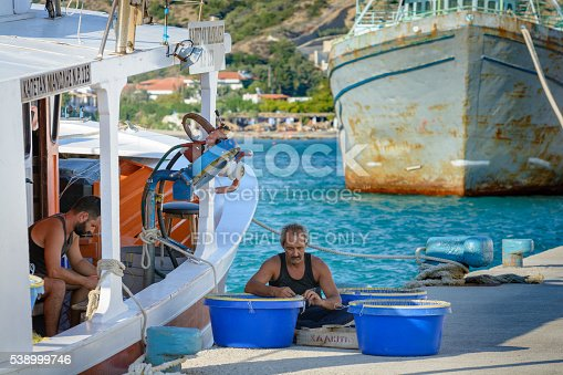 932662672istockphoto Fishermen are sitting at port and sorting their catch 538999746