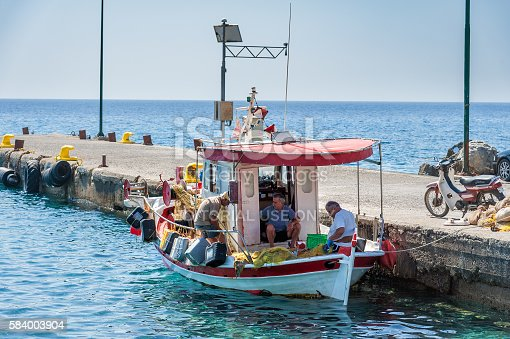 932662672istockphoto Fishermen are sorting their catch at pier of Paleochora town 584003904