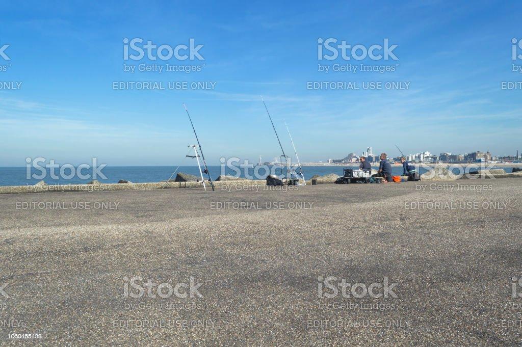 Fishermen At Shveningen Beach Pier Watching Their Fishing Rods And