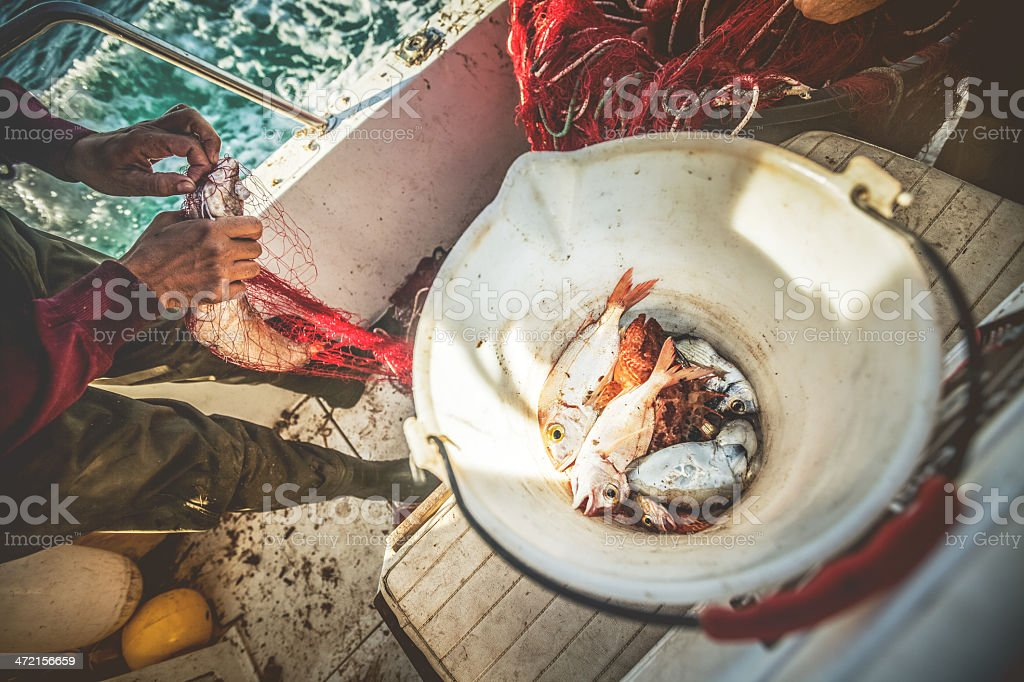 Fishermen at work, cleaning the nets stock photo
