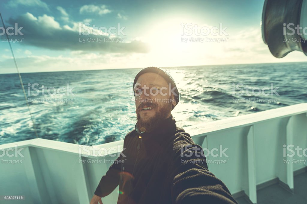 Fishermen at work: selfie from the trawler with sailing stock photo