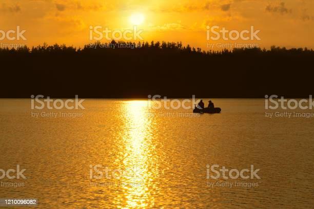 Photo of Fishermen catch fish on the lake at sunset.