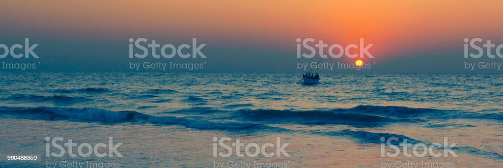 Fishermen come back at sunset stock photo