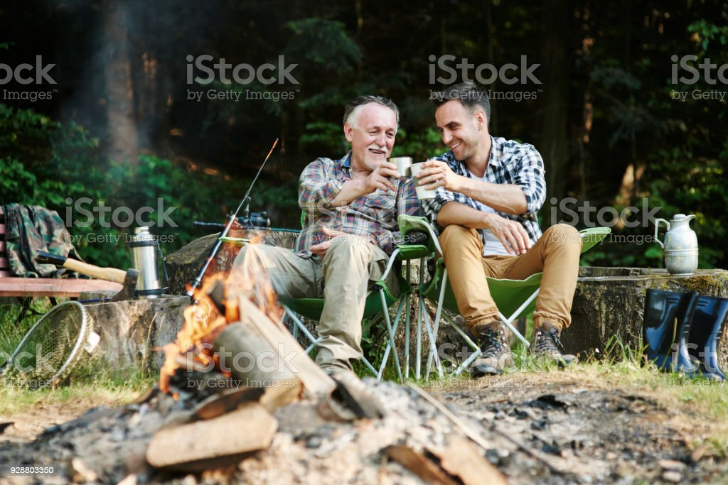 Fishermen drinking coffee beside bonfire stock photo