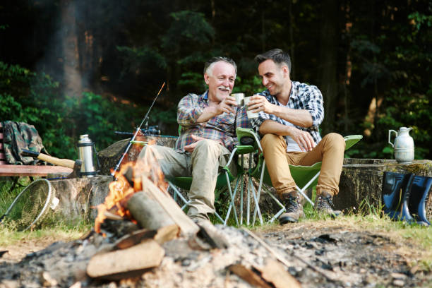 fishermen drinking coffee beside bonfire - camping stock photos and pictures