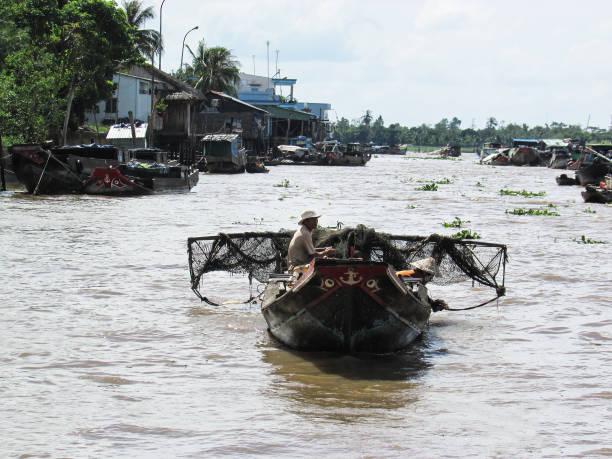 fishermen in a boat over Mekong River in Vietnam stock photo