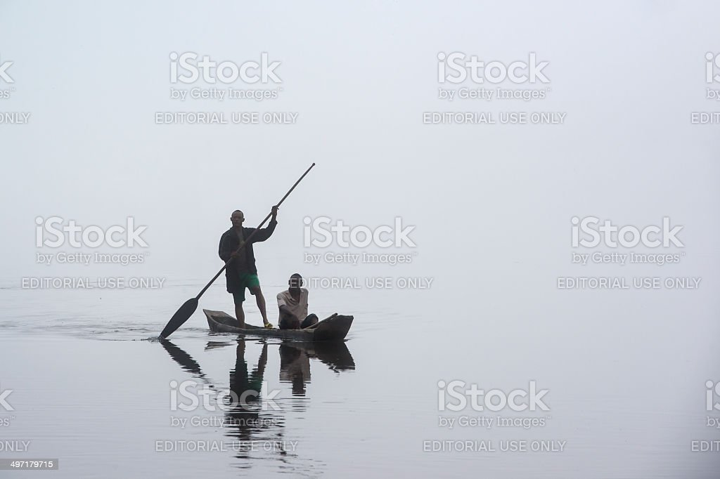 Fishermen in a pirogue on the foggy Congo River stock photo