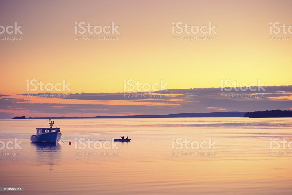 Fishermen in Rowing Boat at Dusk stock photo