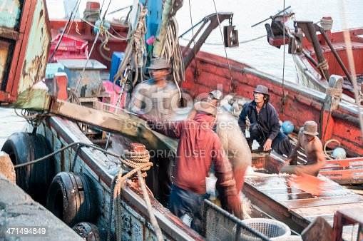 Hua Hin, Thailand - July 12, 2008: Fishermen load ice onto their boat to keep the catch fresh at the tourist resort of Hua Hin in Thailand