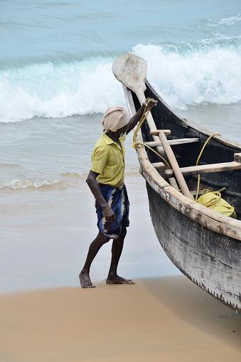 Kovalam, India – April  11, 2015. Fishermen near the boat on the beach of Kovalama, India.