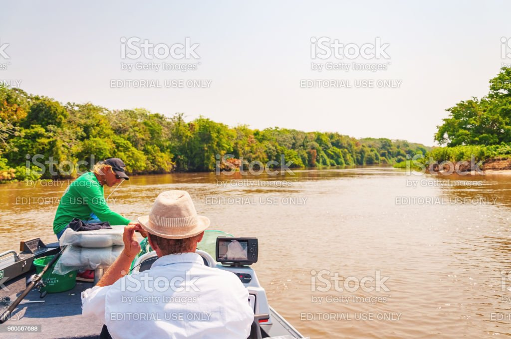 Fishermen on a boat navigating on Rio Paraguai stock photo
