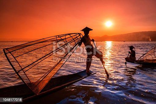 Fishermen on Inle Lake watching the sunset. Leg-rowing fishermen on Inle Lake are a major tourist destination in Myanmar (Burma).